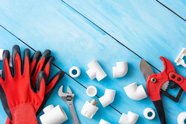 Handschoenen en pijpsnijder met plastic onderdelen voor watervoorziening.