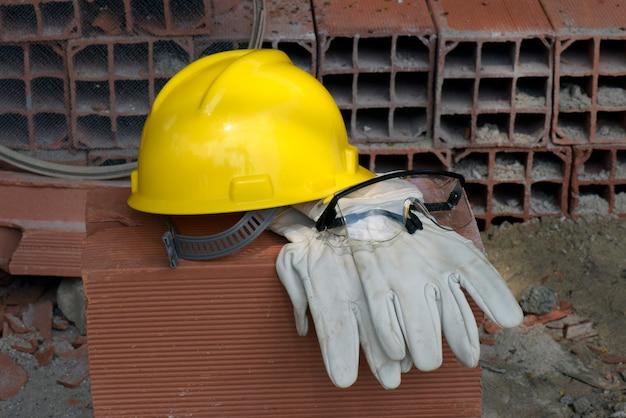 Handschoenen, helm en bril van de metselaar op stapel stenen