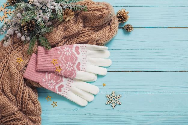 Handschoenen, sjaal en kerstversiering op blauwe houten oppervlak