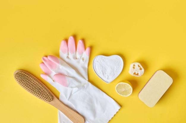 Handschoenen sponzen frisdrank en penseel op gele achtergrond eco reinigingsconcept