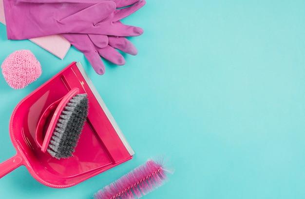 Handschoenen, stoffer, boen en borstel op turkooizen achtergrond