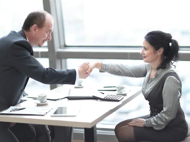 Handshake manager en de klant over een bureau