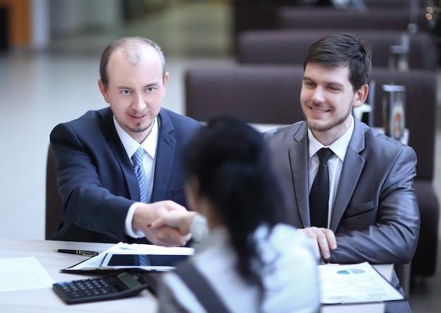 Handshake manager en klant in een modern office.meetings en samenwerkingen.