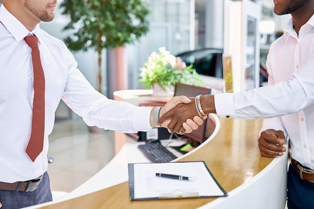 Handshaking van klant en verkoper in autoshowroom close-up