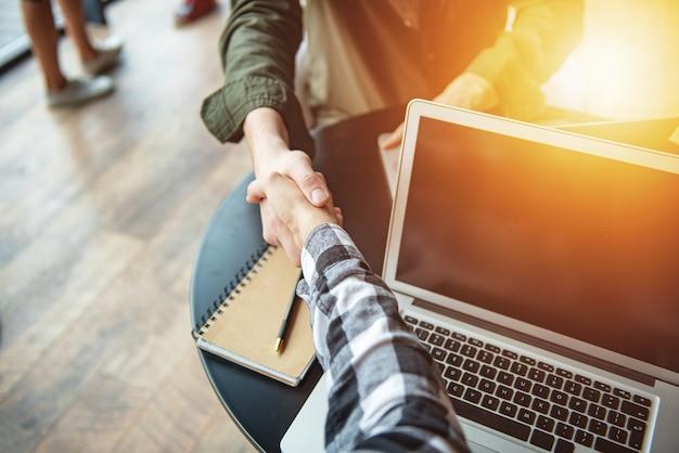 Handshaking zakenman in vrijetijdskleding in het kantoorconcept van teamwork en partnerschap