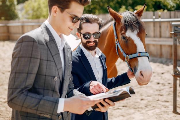 Handsme mannen staan in een ranch