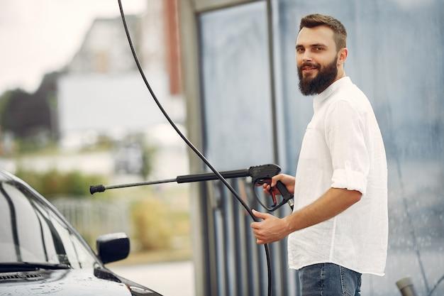 Handsomenmens in een wit overhemd die zijn auto wassen