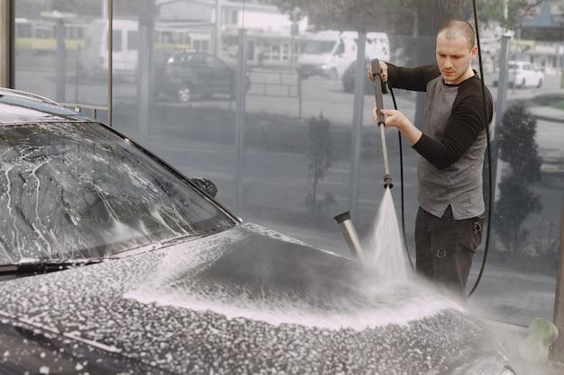 Handsomenmens in een zwarte sweater die zijn auto wassen