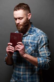 Handsone man lezen en bidden over bijbel in een donkere kamer over grijze textuur