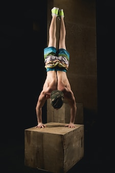 Handstand push-up man training bij sportschool pus ups