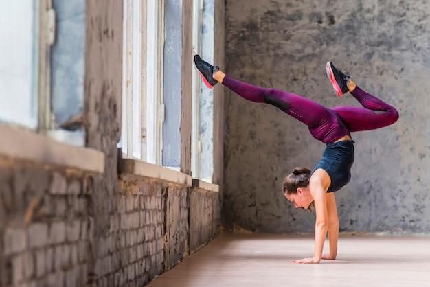 Handstand yogi vrouw beoefenen van yoga naar beneden gerichte boom vormen