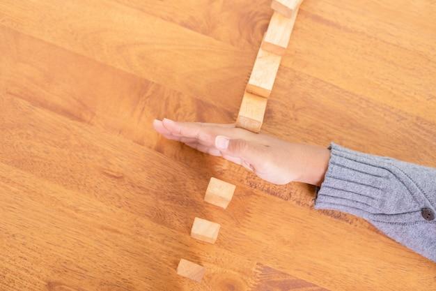 Handstop houten blok, waardoor een domino-risico-effect ontstaat