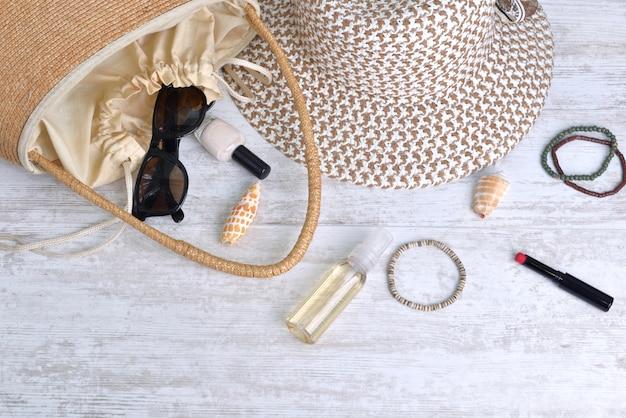 Handtas en hoed met vrouwelijke toebehoren die op witte lijst worden gemorst