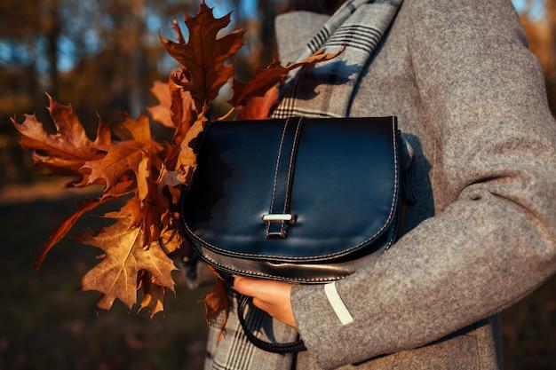 Handtas. jonge vrouw die modieuze beurs houdt en jas draagt