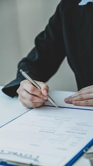 Handtekening op contract nadat de makelaar het zakelijke contract aan de koper heeft uitgelegd.