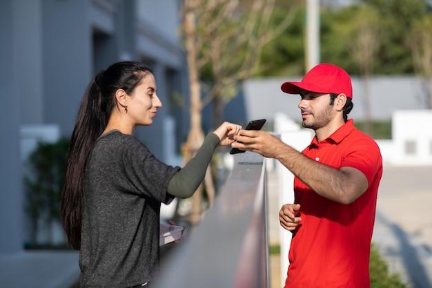 Handtekening op smartphone-apparaat ondertekenen om een pakket te krijgen. mooie vrouw die pakket ontvangt van bezorger in rood uniform thuis.