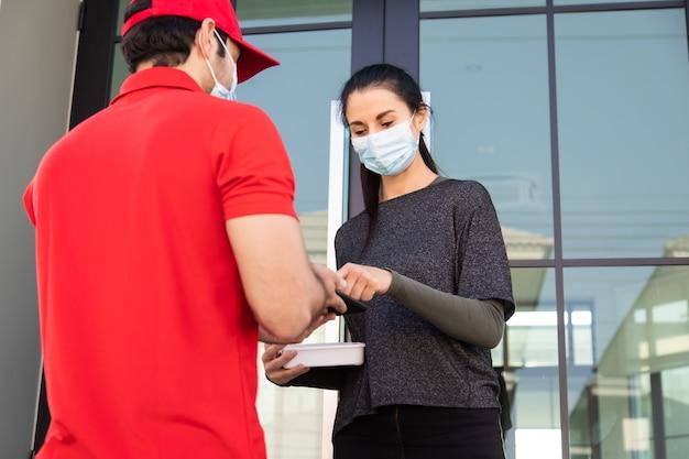 Handtekening op smartphone-apparaat ondertekenen om een pakket te krijgen. vrouw die pakket ontvangt van bezorger in rood uniform