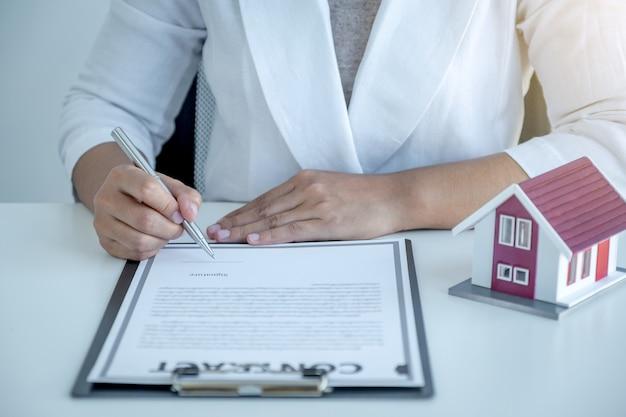 Handtekening van het contract nadat de makelaar het zakelijke contract, de huur, de aankoop, de hypotheek, de lening of de woningverzekering aan de koper heeft uitgelegd