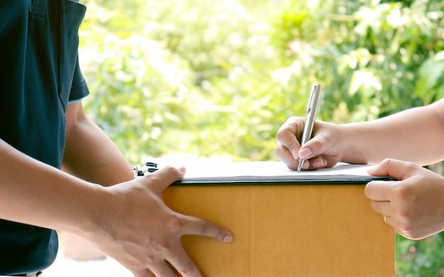 Handtekeningen van klanten op het klembord om pakketten van professionele bezorgers te ontvangen.