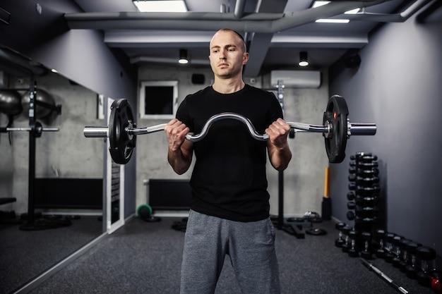 Handtraining met sportartikelen. een portret van de helft van het lichaam van een knappe en gespierde man in de sportschool die zijn biceps traint met een halter. moderne sportschool met een donkere sfeer, sportief leven