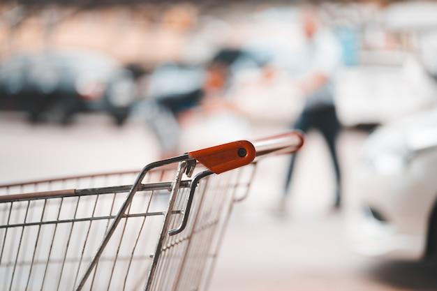 Handvat van winkelwagen en wazig lopende man met kind op parkeerplaats, herfst kleurtint