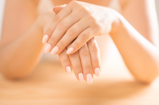 Handverzorging. close-up van mooie vrouwelijke handen met natuurlijke manicure nagels. close-up van de hand van de vrouw aanraken van haar zachte zijdeachtige gezonde huid. schoonheid en gezondheid, lichaamsverzorging concept. selectieve focus