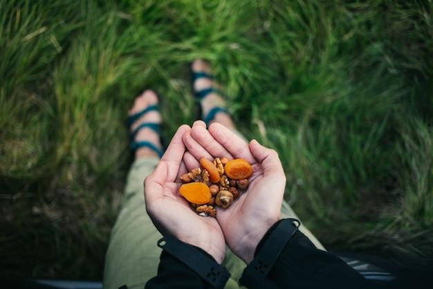 Handvol gezonde noten, rozijnen en gedroogd fruit buiten in de wildernis. snelle snack tijdens wandeling in de bergen.