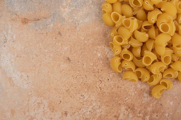 Handvol rauwe onvoorbereide pasta op marmeren achtergrond. hoge kwaliteit foto