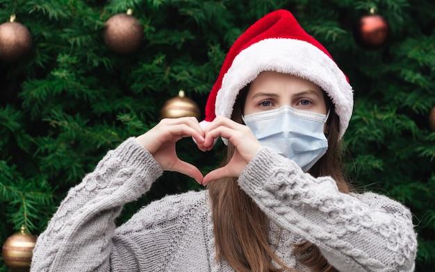 Handvormige hartliefde. sluit omhoog portret van vrouw die een hoed van de kerstman en medisch masker met emotie draagt. tegen de achtergrond van een kerstboom. coronapandemie