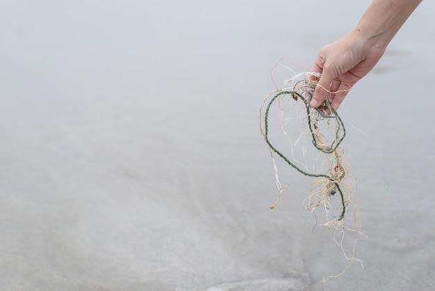 Handvrouw die het plastic netto schoonmaken op het strand opnemen