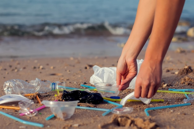 Handvrouw die plastic flessen schoonmaken op het strand, vrijwilligersconcept oppakken