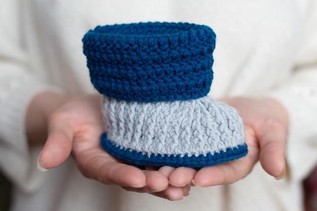 Handwerk blauw en wit gebreide slofjes op handen