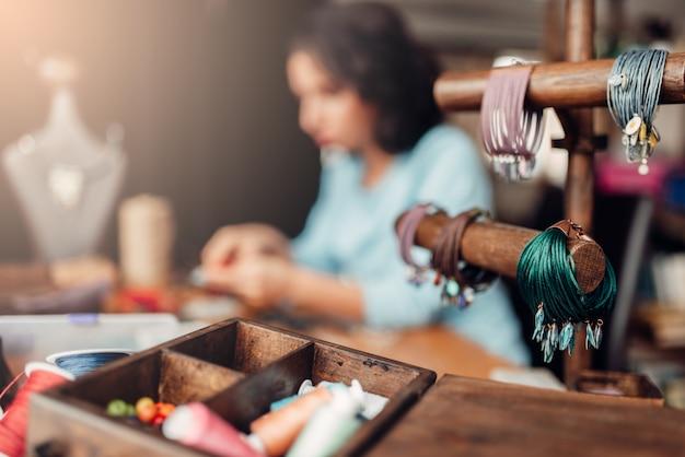 Handwerk, doos met accessoires, armbanden, vrouwelijke meester op werkplek in werkplaats