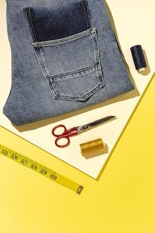 Handwerk, kledingreparatie. geripte spijkerbroek naaiaccessoires met kleurrijke achtergrond van bovenaf. plat leggen