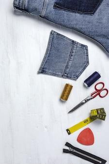 Handwerk, kledingreparatie. gescheurde jeans naaiaccessoires van bovenaf. plat leggen