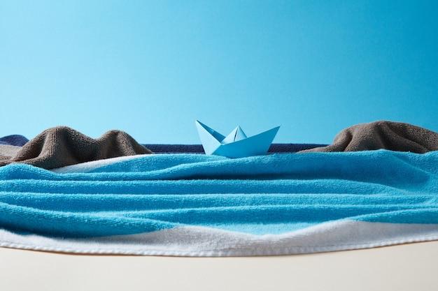 Handwerk zee golven en stenen rotsen gemaakt van pluizige handdoeken en blauw schip op een papieren achtergrond met kopieerruimte.