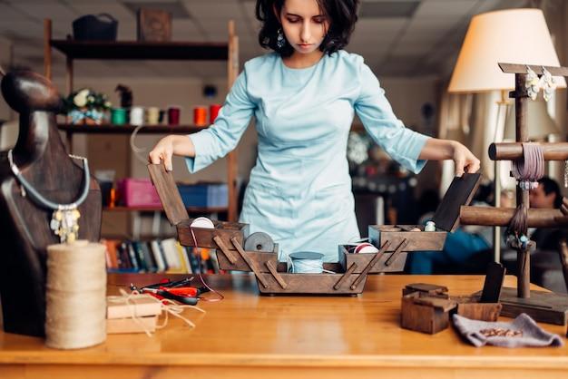 Handwerkgereedschap en uitrusting, vrouwelijke meester op werkplek in werkplaats. ambachtelijke accessoires. handgemaakte mode-inrichting