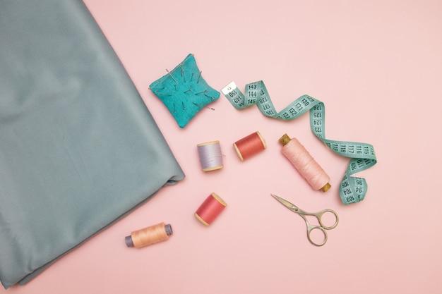 Handwerkhulpmiddelen, gebreide naaldpunt voor het naaien, schaar en gekleurde spoelen van draad op een roze achtergrond met copyspace voor tekst