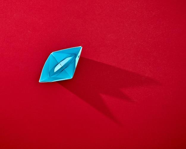 Handwerkpapier blauw schip geïsoleerd op rode achtergrond met reflectie van schaduwen en kopieer ruimte. bovenaanzicht