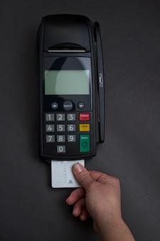Handwisselen van creditcard in de winkel. vrouwelijke handen met creditcard en bank terminal. kleurafbeelding van een pos en creditcards.