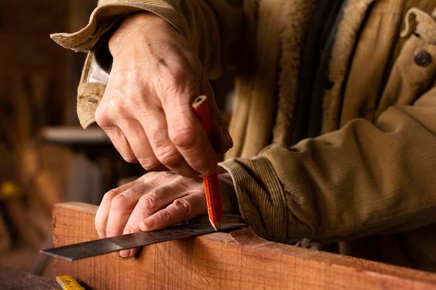 Handyman die een potloodlijn op hout maakt