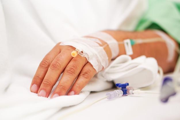 Handziek met de zoute aziatische patiënt van de zoute zoute waterlijn op bed in de verpleegsterziekenhuisafdeling.