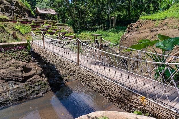 Hangbrug in de jungle in de buurt van de rijstterrassen op het eiland bali, indonesië. natuur- en reisconcept