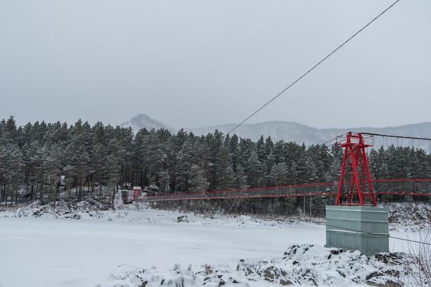 Hangende brug boven de winter bevroren rivier