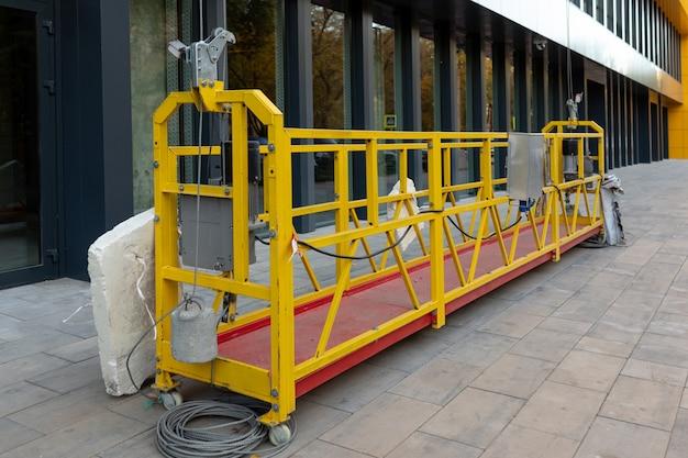 Hangende constructiewieg na beglazing van de gevel van een commercieel object staat op de grond technische stedelijke achtergrond