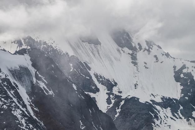 Hangende gletsjer op grote berg in lage wolken.