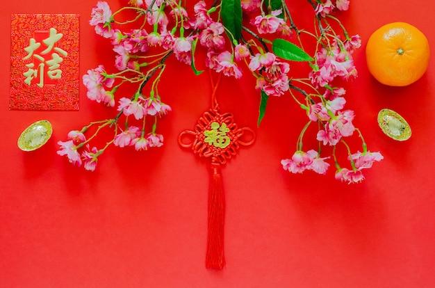 Hangende hanger voor chinees nieuwjaarsornament (woord betekent rijkdom) met rood enveloppakket of ang bao (woord betekent auspiciën), goudstaven, oranje en chinese bloesembloemen op rode achtergrond.