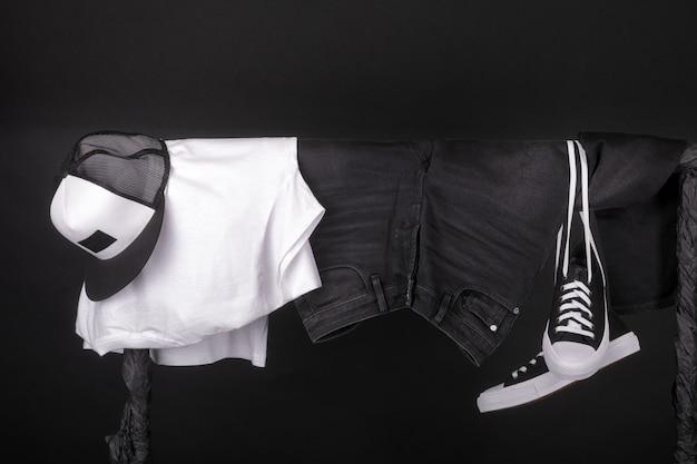 Hangende kleding. zwart-witte sneakers, pet en jeans op kledingrek op zwart.