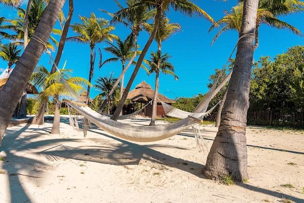 Hangende lege hangmat met boot en kano op zand bij mooi mexicaans strandtoevlucht