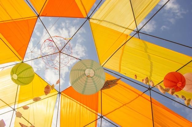 Hangende papieren bollampen voor een feest met een blauwe hemelachtergrond.